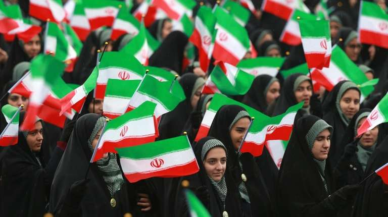 Iranians with national flags during a ceremony celebrating