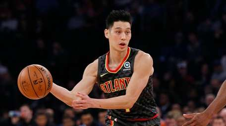 Jeremy Lin passes the ball around Knicks guard