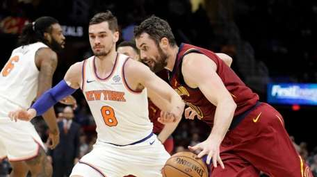 Cleveland Cavaliers' Kevin Love (0) drives past New