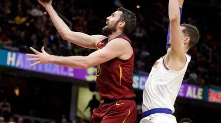Cleveland Cavaliers' Kevin Love, left, drives to the