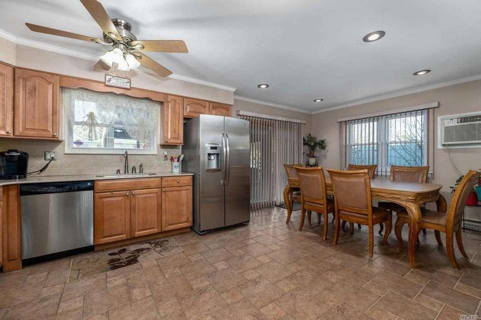 The kitchen features custom tile work, stainless steel