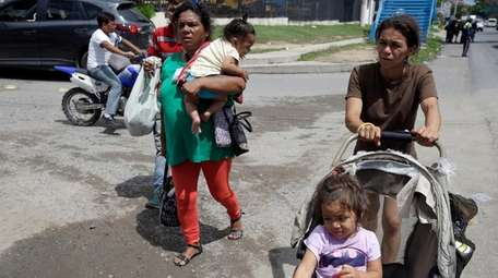 A couple of Honduran migrant mothers carry their