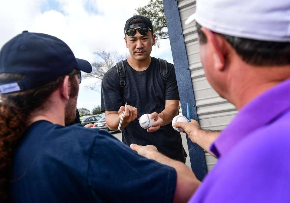 Yankees pitcher Masahiro Tanaka signs autographs for fans