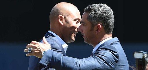 Derek Jeter congratulates Jorge Posada during a ceremony