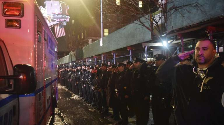 Members of the NYPD salute the ambulance carrying