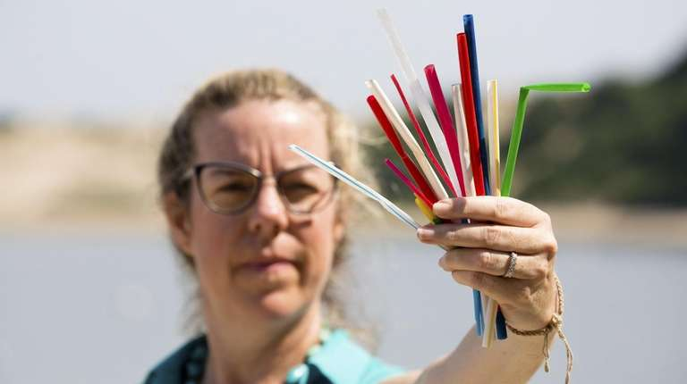 Holding plastic straws from a previous beach cleanup,