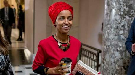 Rep. Ilhan Omar, D-Minn., center, walks through the