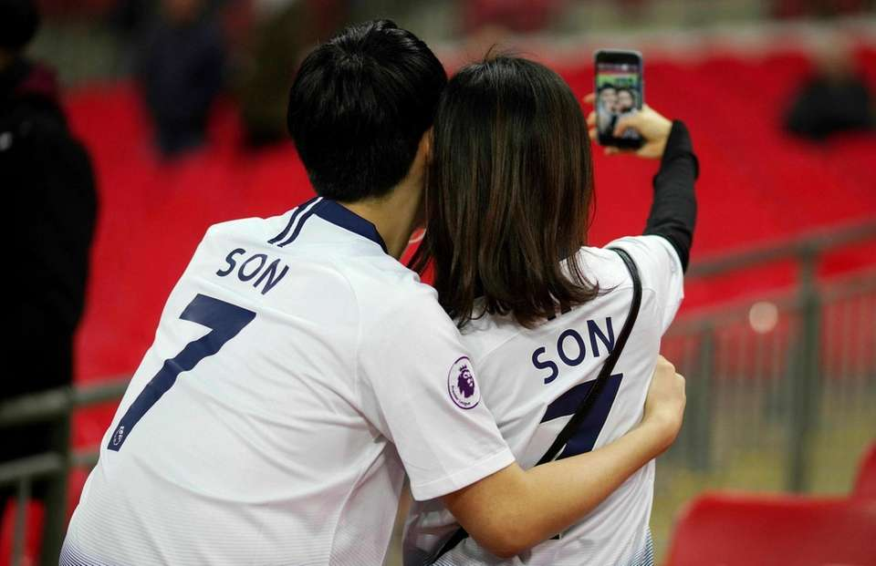 Tottenham Hotspur fans take a selfie before the