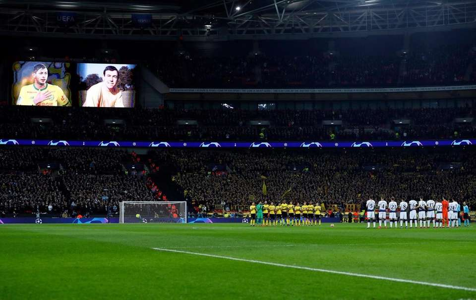 Dortmund, left, and Tottenham players stand during a