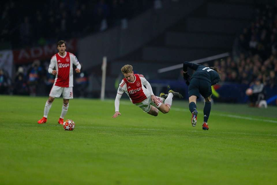 Ajax's Rasmus Kristensen, center, is tackled by Real