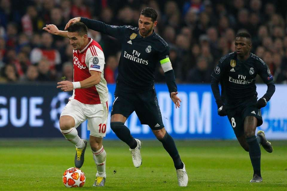 Ajax's Dusan Tadic, left, fights for the ball