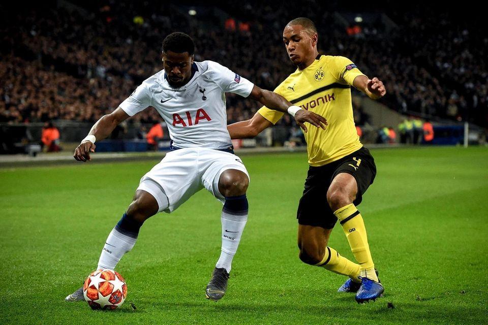 Tottenham's Serge Aurier (L) in action against Dortmund's