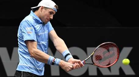 John Isner returns to Bernard Tomic during the