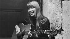 Singer-songwriter Joni Mitchell strums her guitar outside The