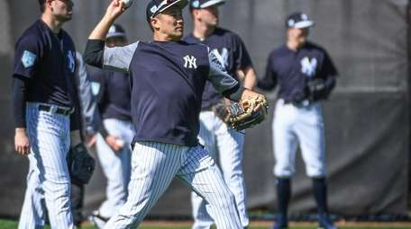 New York Yankees Masahiro Tanaka, center, along with