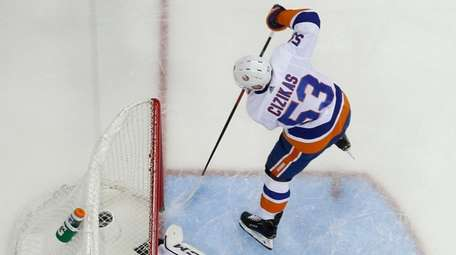 Islanders' Casey Cizikas, top, scores a goal against