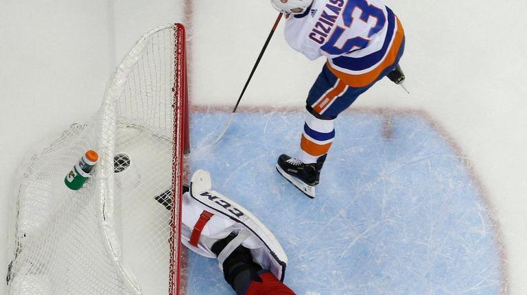 New York Islanders' Casey Cizikas, top, scores a