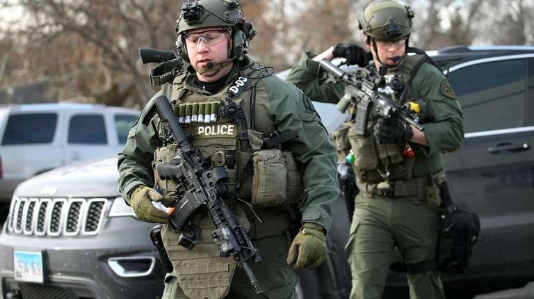 Police officers armed with rifles gather at the