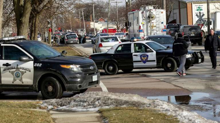 Law enforcement personnel gather near the scene of