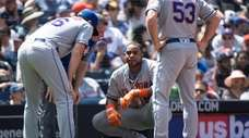 The Mets' Yoenis Cespedes, center, gets his injury