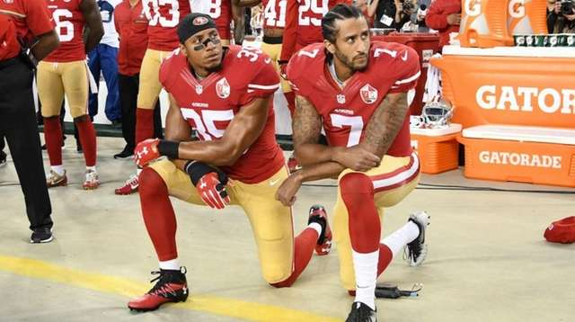 Colin Kaepernick, right, and Eric Reid kneel during