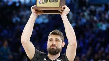 The Nets' Joe Harris holds the champion trophy