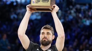 The Nets' Joe Harris holds the champion trophy