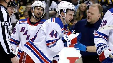 Rangers' Neal Pionk (44) is helped off the