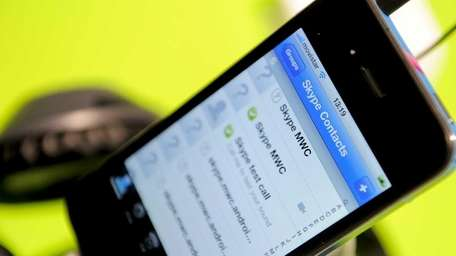 A mobile phone shows a Skype application at