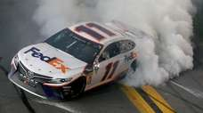 Denny performs a burnout after winning the Monster