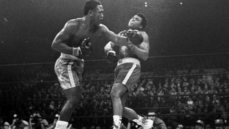 Joe Frazier hits Muhammad Ali with a left