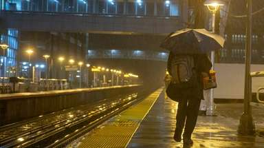 Commuters in the rain at the Mineola LIRR