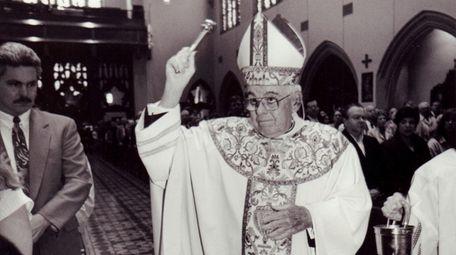 Bishop John McGann blesses parishoners with holy water