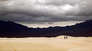 Visitors walk across dunes at White Sands National