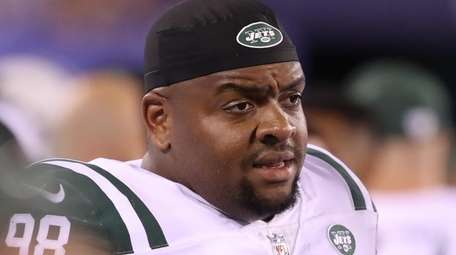 Jets defensive lineman Mike Pennel watches from the