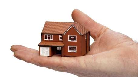 Hand holding a miniature modern detached house isolated