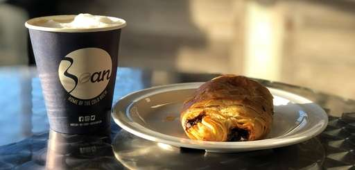 A latte and chocolate croissant at Babylon Bean