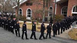 NYPD officers walk into the funeral for NYPD