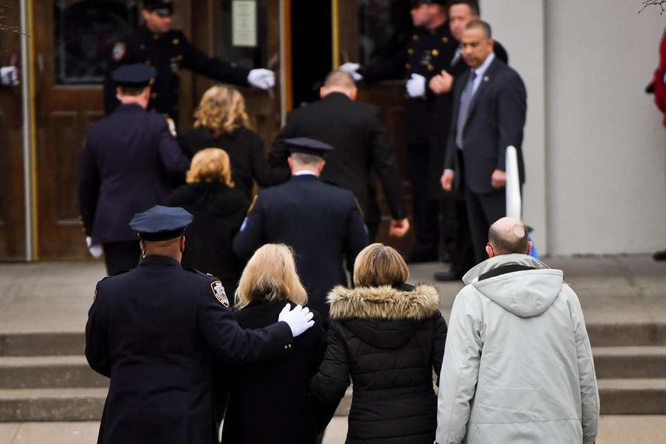 NYPD friends and family walk into the funeral