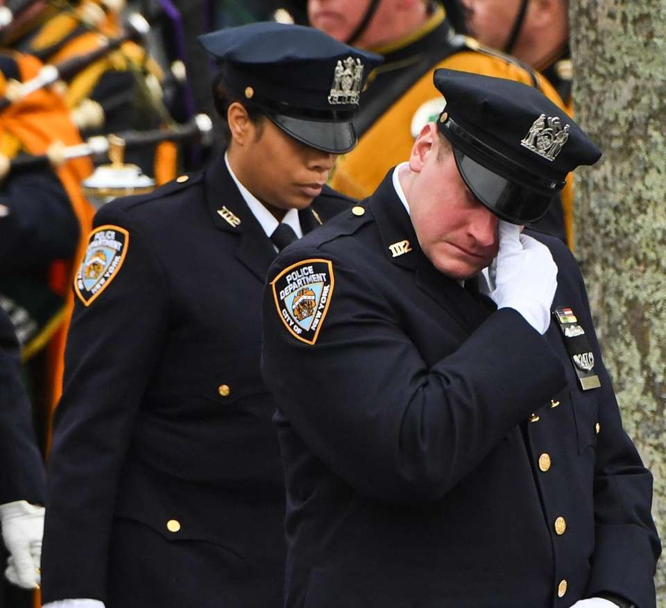 NYPD officers walk from the church after the