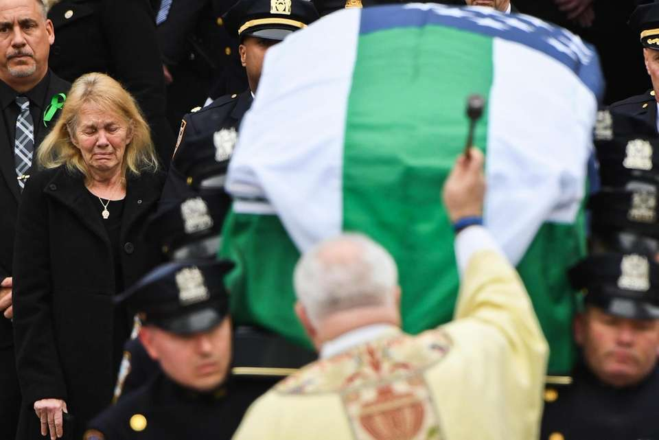 NYPD officers carry the coffin of Det. Brian