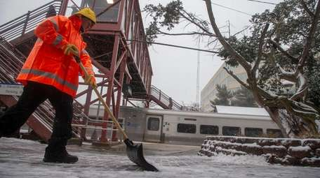 A Long Island Rail Road worker clears the