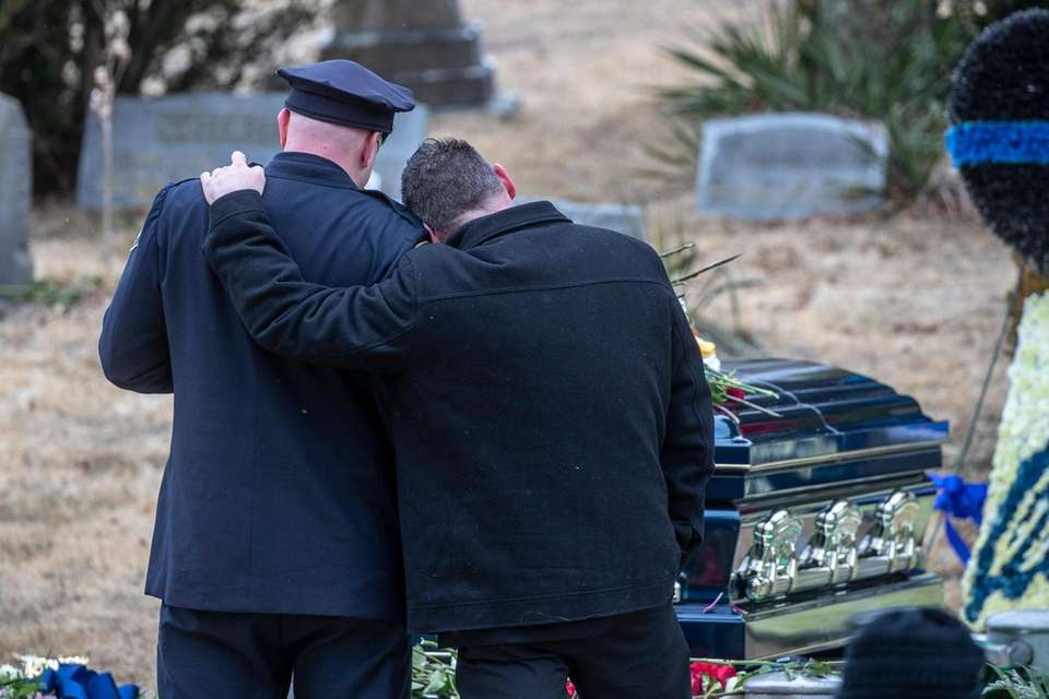 Mourners at the gravesite for NYPD Det. Brian