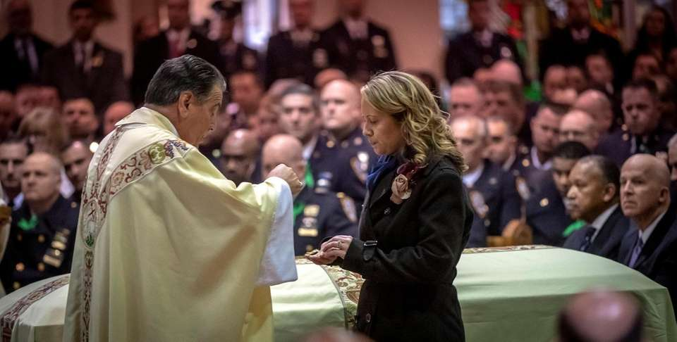 NYPD Chaplain Monsignor David Cassato sharing communion with