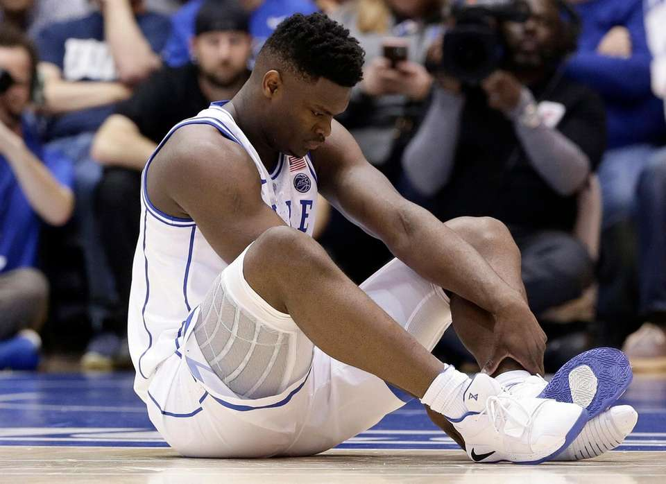 Duke's Zion Williamson sits on the floor following