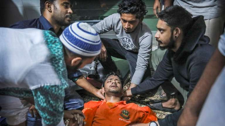 Locals help a Bangladeshi firefighter who lost consciousness