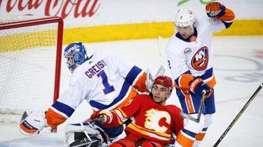 The Islanders' Nick Leddy, right, checks the Flames'