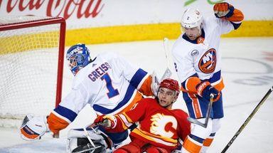 The Islanders' Nick Leddy, right, checks the Flames'