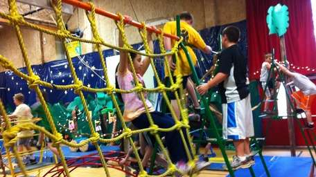 Fourth-grader Darcee Mullins climbs across a rope wall