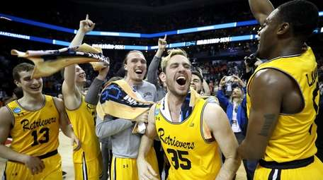 The UMBC Retrievers bench reacts to their 74-54